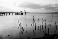 Long exposure view of a pier on a lake at sunset, with soft tone. S, perfectly still water and fishing nets and poles in the foreground Stock Photos