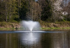 Long Exposure Water Fountain Reflecting in a Lake Royalty Free Stock Photos