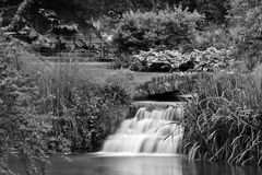 Waterfall in the Bishops in Wells. Long exposure of the waterfall flowing through the garden in the Bishops palace in Wells.black and white Royalty Free Stock Photos