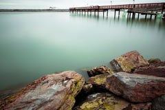 Long exposure winter dock and rocks Stock Image