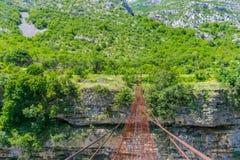 Long extreme suspension iron bridge across the river Moraca Stock Photography