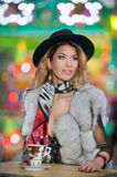 Long fair hair young beautiful woman with black hat, scarf and fur coat, outdoor shot in a cold winter day. Attractive blonde girl. In winter clothes drinking Stock Image