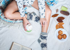 Long female feet in warm woolen socks around her is a book she reading it. Morning with cup Stock Images