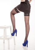 Long female legs in black stockings and blue shoes Royalty Free Stock Images
