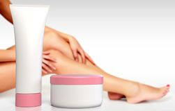 Long female legs and hands with anti-cellulite cream. In tube and jar Royalty Free Stock Images