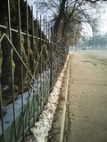 Long fence along a deserted street of a winter weekend royalty free stock photos