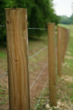 Long fence of wooden posts 2. Long fence of wooden posts and wire stock image