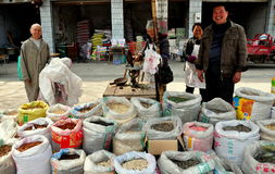 Long Feng, China: Family Selling Dried Foods. Family members displaying a large variety of seeds, nuts, and spices in plastic bags on the sidewalk in front of stock image