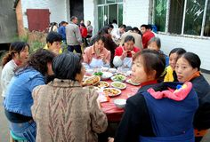 Long Feng, China: Luncheon Guests at Party. Friends and neighbours celebrate a young man's special 19th birthday luncheon eating at large round tables spread royalty free stock images