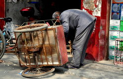 Long Feng, China: Man Repairing Bicycle Cart. A Chinese man fixing a bicycle cart turned on its side in front of his small repair shop in Long Feng, China stock images