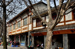 Long Feng, China: Outdoor Card Players. A group of people playing cards next to one of the distinctive wood and stucco buildings lining the main street of Long royalty free stock photos