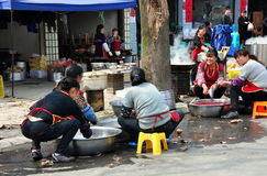 Long Feng, China: Restaurant Workers. A group of women workers cleaning fish and washing dishes in front of a small restaurant in Long Feng, China royalty free stock photos