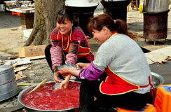 Long Feng, China: Women Cleaning Fish. Two Chinese women seated on plastic stools cleaning freshly caught fish in a large metal bowl sitting in front of a stock images