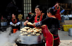 Long Feng, China: Women Preparing Food. Two women serving up portions of steamed pork and potatoes from a large metal steaming vat at a popular local restaurant stock photography
