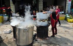 Long Feng, China: Women Preparing Food. Steam rises from huge metal pots where two women are cooking chicken and pork at a popular local restaurant in Long Feng stock photo