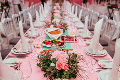 Long festive table served dishes and decorated with branches of greenery. Wedding banquet. Stock Images