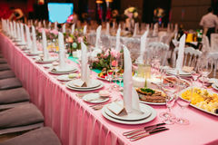 Long festive table served dishes and decorated with branches of greenery. Wedding banquet. Stock Image
