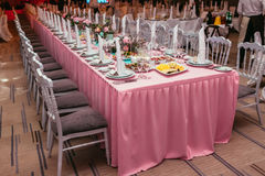 Long festive table served dishes and decorated with branches of greenery. Wedding banquet. Stock Photos