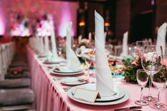 Long festive table served dishes and decorated with branches of greenery. Wedding banquet. Royalty Free Stock Image