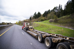 Long flat bed step down trailer on semi truck Royalty Free Stock Images