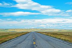 Long flat road traveling through Montana. Royalty Free Stock Image