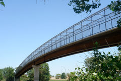 Long footbridge. Architectural details of long, curving footbridge in park Stock Photo