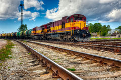 Long freight train. A photo of a long and powerful locomotive and many round barrel carriage on railway on a cloudy day Stock Photography