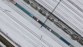 Long freight train coming on the railroad station in winter. Aerial shoot. stock video