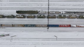 Long freight train coming on the railroad station in winter. Aerial shoot. stock footage