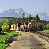 Long freight train. Long freight train after famous spiral tunnels goes from Vancouver to Calgary on June 09, 2011 in Lake Louise, Canada Royalty Free Stock Photo