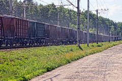 Long freight train with freight cars goes by rail. Brown iron wagons as part of a train traveling by rail Stock Image