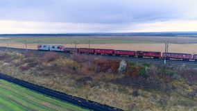 A freight train moves away along an embanked track. A long freight train moves away from the camera along its way in empty fields stock video footage