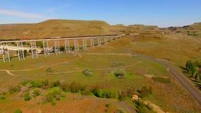 Long freight train travels railroad Trestle Bridge Lyons Ferry. Aerial view slides right through lush Snake River Valley near Lyon`s Ferry Washington stock video footage