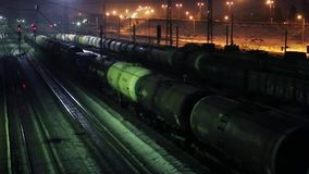 Long freight trains move on railway at winter night. PERM, RUSSIA - MAR 7, 2015: Long freight trains move on railway at winter night stock video footage