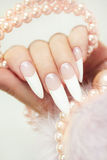 Long French manicure. Long French manicure with pearls and the fur on a gray background stock image