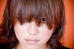 Long fringe. A closeup of a young woman with her long fringe obscuring her face stock photo