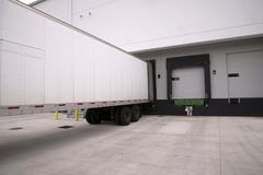 Long dry van semi trailer stand with open door in warehouse dock. Long full-sized semi trailers stand it row at the dock gates of a large industrial warehouse Royalty Free Stock Photo