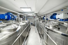 A long gangway between two rows of cisterns. Storage of food liquids. Royalty Free Stock Photos