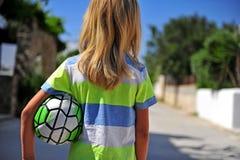 Long garçon de cheveux blonds avec le football photo libre de droits