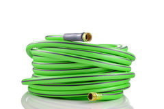 Long garden hose rolled-up on white. Background royalty free stock photography