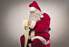 Long Gift List. Santa Claus reading a long gift list Royalty Free Stock Photo