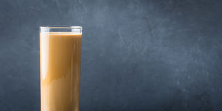 Long glass with coffee and cream on dark background. Banner Stock Images