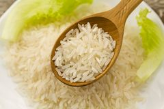 Long grain rice in a wooden spoon on a background plate, green salad. Healthy eating, diet Stock Photo
