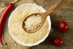 Long grain rice in a wooden spoon on a background plates, chili pepper, cherry tomato. Healthy eating, diet Stock Photos