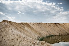 Long gravel dune. Gravel hill in sky background. Excavated soil in quarry. Gravel and sand extraction industry Royalty Free Stock Photo
