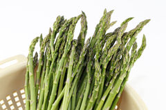 Long Greens. Delicious asparagus spear vegetables drain in a colander for a recipe Stock Photos