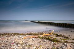 Long groynes protrude into the water of the blue Baltic Sea stock photos