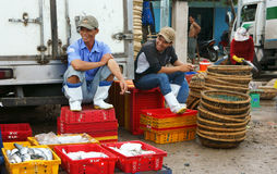 Two man relax at fishing market. LONG HAI, VIET NA Stock Photo