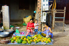 Long Hai, Vung Tau, Vietnam - Dec 29, 2014: Mother and her child sell local fruits at Long Hai fish market in early morning Stock Photos