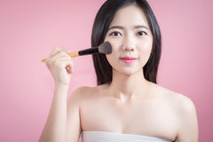 Long hair asian young beautiful woman applying cosmetic powder brush on smooth face  over pink background. natural makeup. Royalty Free Stock Photography